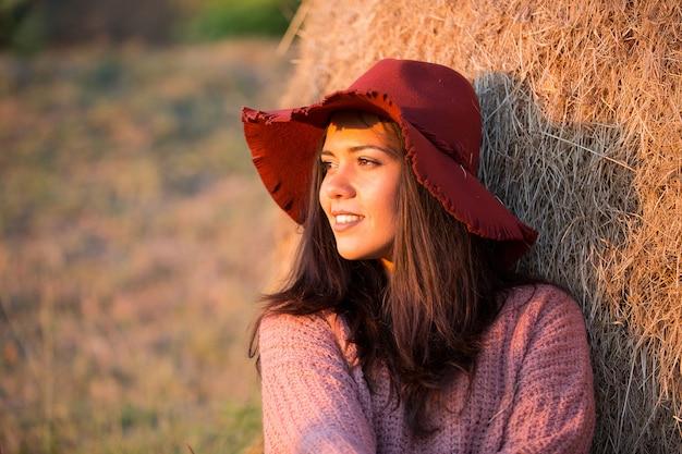 Seitenansichtporträt einer schönen jungen frau mit stilvollem hut bei sonnenuntergang mit weinberg und strohballen hinter ihr.