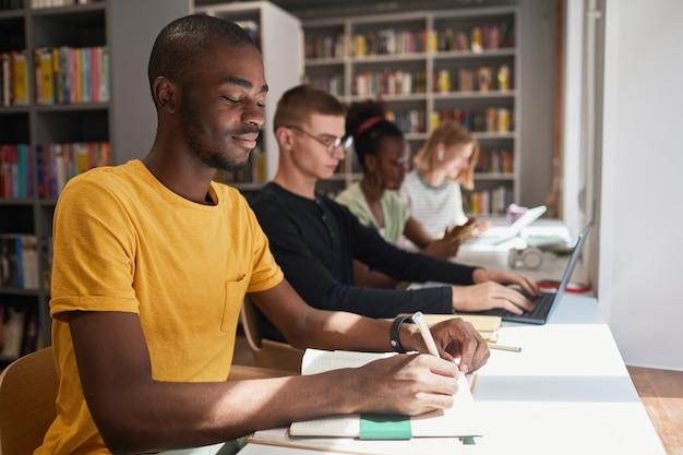 Seitenansichtporträt einer verschiedenen gruppe von studenten, die beim lernen in der schulbibliothekskopie in reihe sitzen...