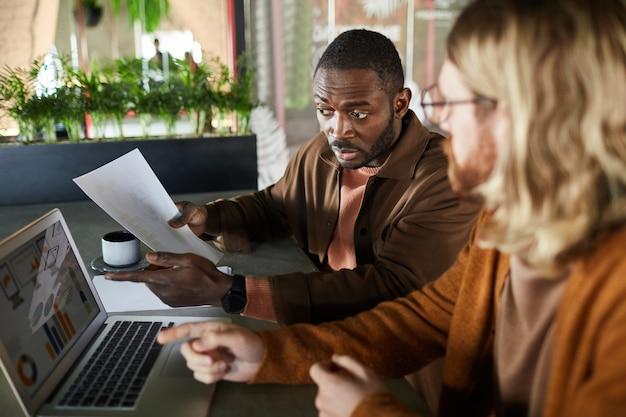 Seitenansichtporträt eines afroamerikanischen mannes, der aktiv mit einem kollegen oder partner spricht und während eines geschäftstreffens im grünen innenraum auf den laptop-bildschirm zeigt, kopierraum