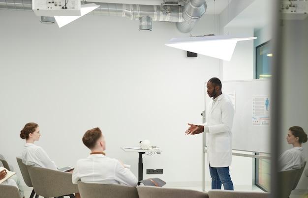 Seitenansichtporträt eines afroamerikanischen mannes, der am whiteboard steht, während er während des medizinischen seminars im college eine präsentation hält, platz kopieren