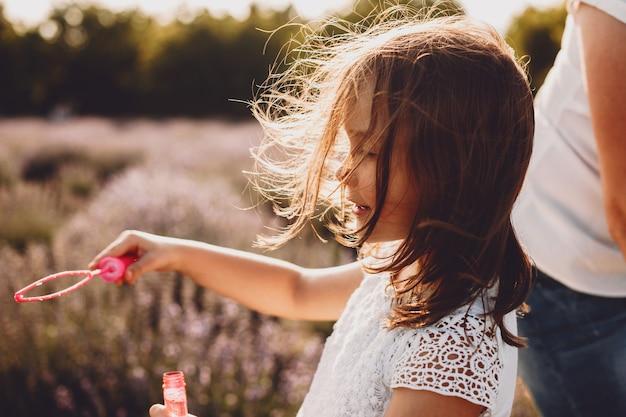 Seitenansichtporträt eines charmanten kleinen mädchens, das seifenballons tut, die gegen sonnenuntergang in einem feld der blume lächeln, während wind ihr haar bläst.
