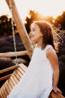 Seitenansichtporträt eines erstaunlichen kleinen mädchens gekleidet im weißen kleid sitzend auf einer hölzernen schaukel, die weg lächelnd gegen sonnenuntergang schaut.