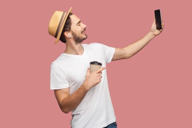 Seitenansichtporträt eines gutaussehenden bärtigen jungen hipster-mannes in weißem hemd und lässigem hut posiert und macht selfie-foto mit lächeln, blogger-lifestyle. innen, isoliert, studioaufnahme, rosa hintergrund