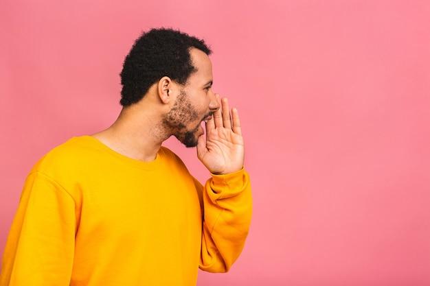 Seitenansichtporträt eines jungen mannes, der laut mit der hand an seinem mund schreit, der auf rosa lokalisiert wird.