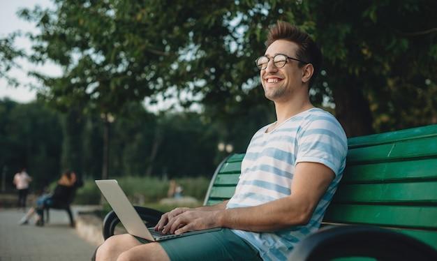 Seitenansichtporträt eines jungen selbstbewussten männlichen freiberuflers, der an seinem laptop arbeitet, während er auf einem strand im park sitzt und lächelnd wegschaut.