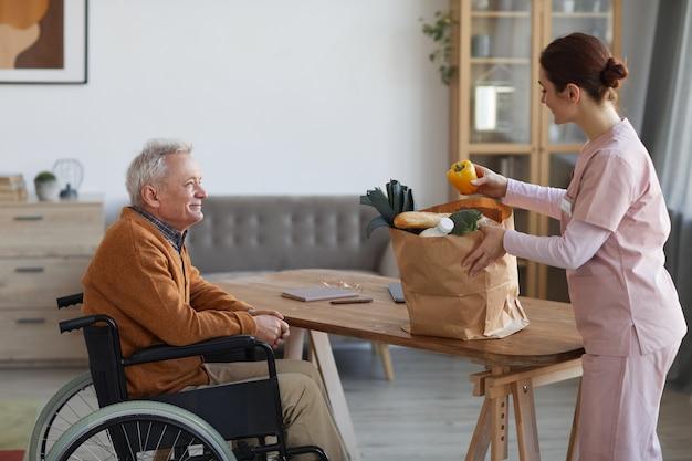 Seitenansichtporträt eines lächelnden älteren mannes im rollstuhl, der weibliche krankenschwester anschaut, die lebensmittel, hilfe und essenslieferungskonzept bringt