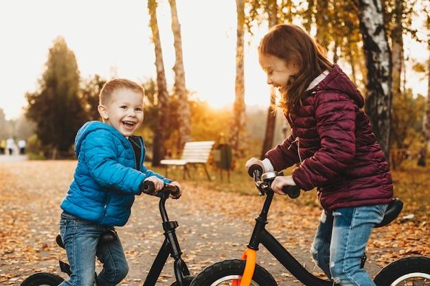 Seitenansichtporträt eines niedlichen bruders und einer schwester, die von angesicht zu angesicht mit ihren fahrrädern sitzen, die draußen im park lachen.
