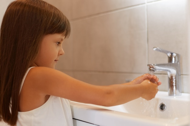 Seitenansichtporträt eines süßen weiblichen kindes mit dunklem haar, das ein weißes, ärmelloses t-shirt trägt, im badezimmer in der nähe des waschbeckens posiert und sich vor dem zubettgehen die hände wäscht.