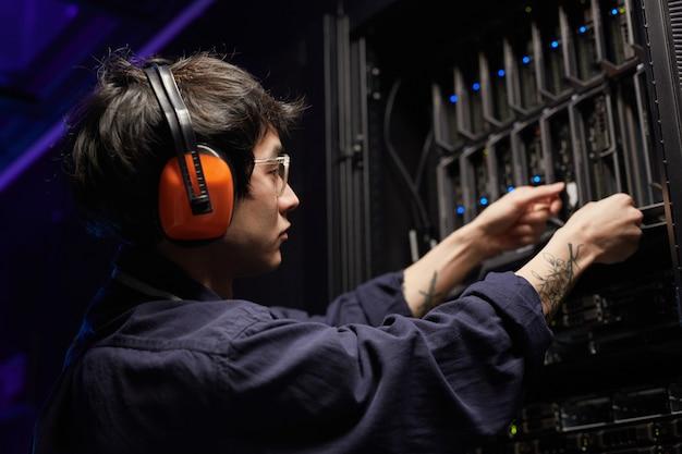 Seitenansichtporträt eines tätowierten jungen netzwerkingenieurs, der server im supercomputer-rechenzentrum einrichtet, platz kopieren