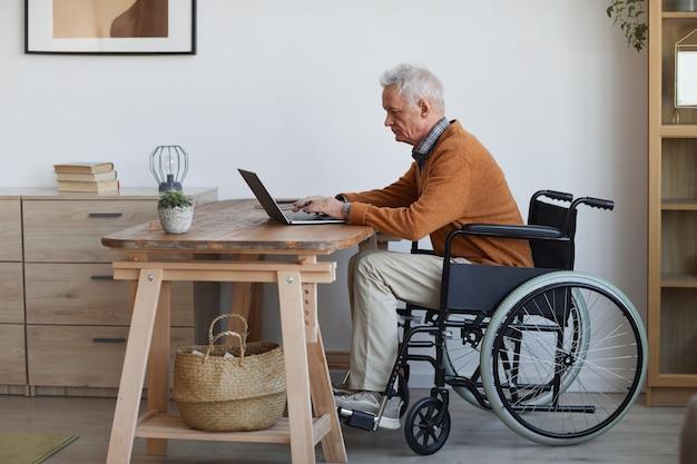 Seitenansichtporträt in voller länge eines älteren mannes im rollstuhl mit laptop zu hause, kopierraum
