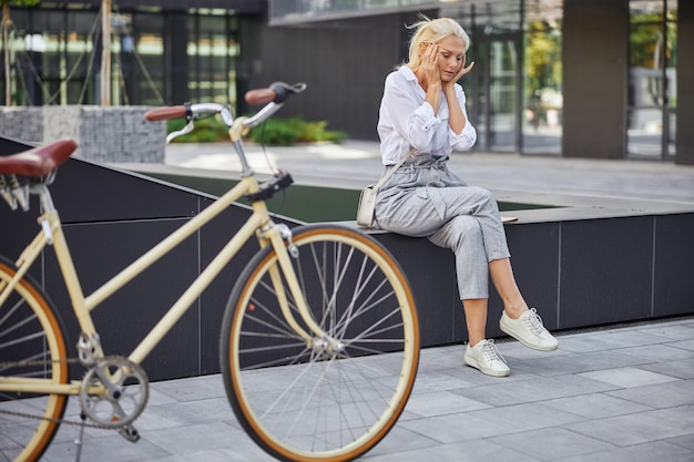 Seitenansichtporträt in voller länge von stilvollen weiblichen kopfschmerzen beim sitzen im freien über dem fahrrad