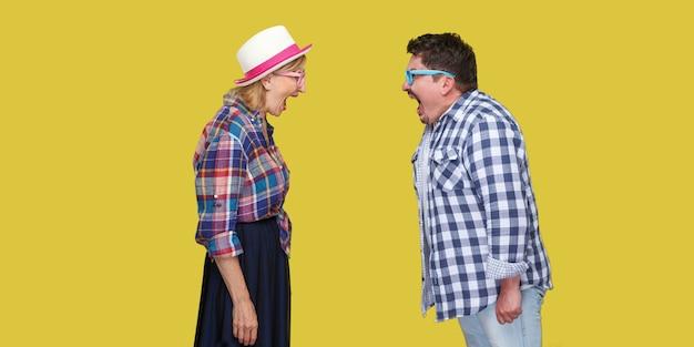 Seitenansichtporträt von ein paar freunden, erwachsenen männern und frauen in lässig kariertem hemd, die zueinander stehen und mit geöffnetem mund schreien. innen, isoliert, studioaufnahme, gelber hintergrund