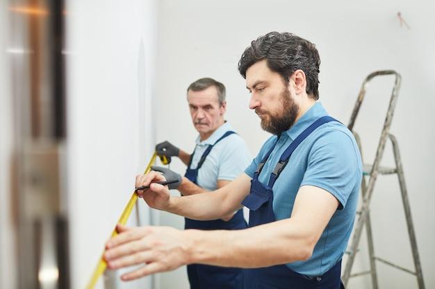 Seitenansichtporträt von zwei bauarbeitern, die wand beim renovieren des hauses messen, raum kopieren