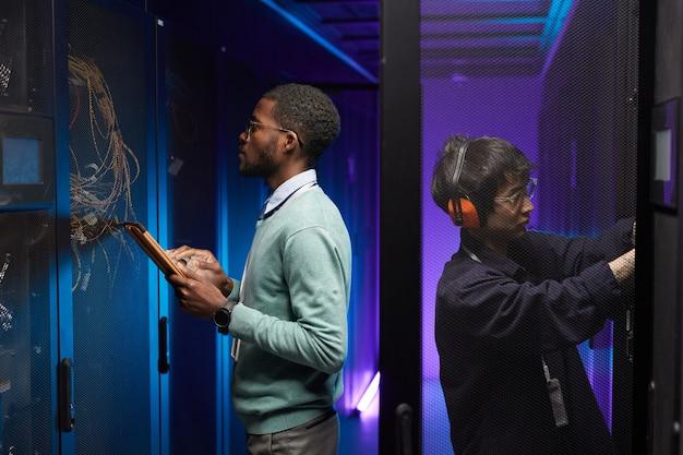 Seitenansichtporträt von zwei technikern, die ein computernetzwerk einrichten, während sie im rechenzentrum arbeiten