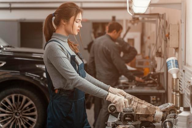 Seitenansichtsfrau, die an einem autoservice arbeitet