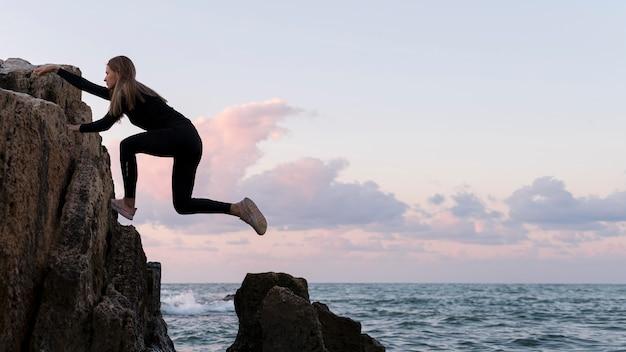 Seitenansichtsfrau, die an einer küste klettert