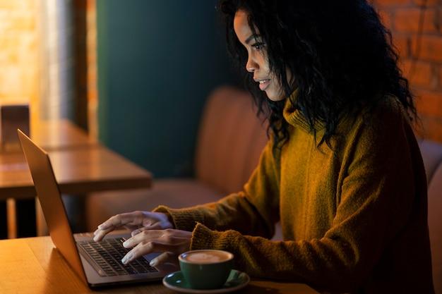Seitenansichtsfrau, die an ihrem laptop in einem kaffeehaus arbeitet
