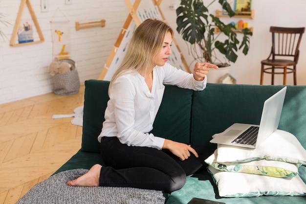 Seitenansichtsfrau, die auf couch arbeitet