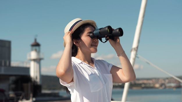 Seitenansichtsfrau, die durch fernglas schaut