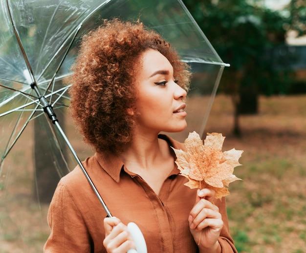 Seitenansichtsfrau, die ein blatt und einen regenschirm hält