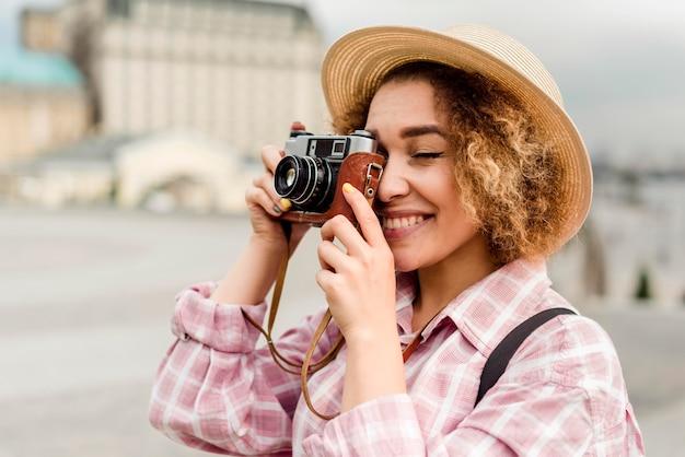 Seitenansichtsfrau, die ein foto während des reisens macht