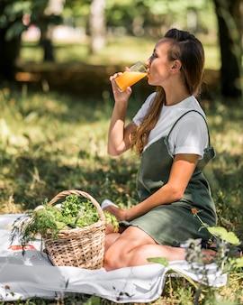 Seitenansichtsfrau, die ein picknick mit gesunden snacks hat