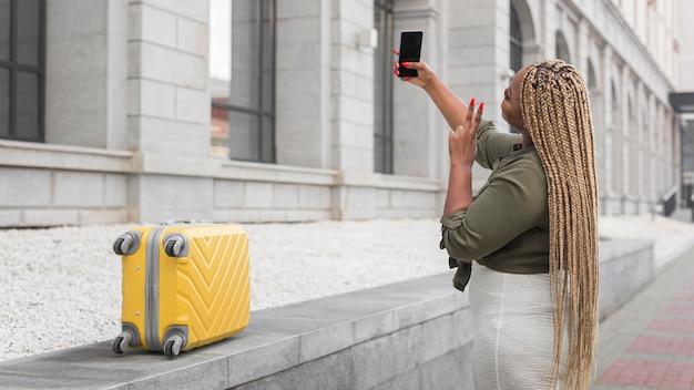 Seitenansichtsfrau, die ein selfie nimmt, während sie mit kopienraum reist
