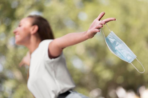Seitenansichtsfrau, die eine medizinische maske hält