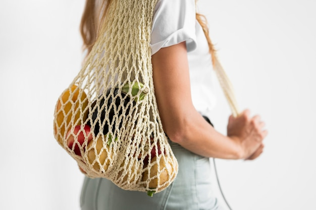 Seitenansichtsfrau, die eine recycelbare tasche hält