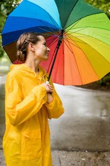 Seitenansichtsfrau, die einen bunten regenschirm hält