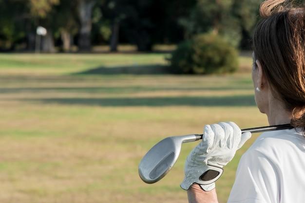 Seitenansichtsfrau, die golf spielt