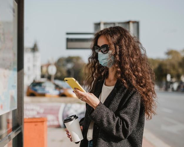 Seitenansichtsfrau, die im busbahnhof wartet