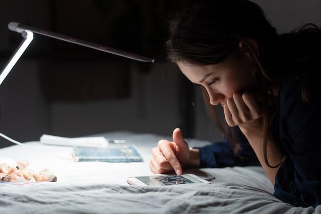 Seitenansichtsfrau, die im dunklen schlafzimmer arbeitet.