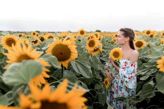 Seitenansichtsfrau, die im sonnenblumenfeld aufwirft