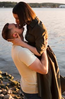 Seitenansichtsfrau, die mann auf nase küsst
