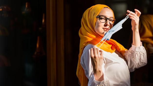Seitenansichtsfrau, die medizinische maske hält
