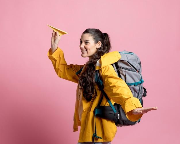 Seitenansichtsfrau, die mit einem papierflugzeug spielt