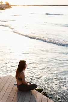 Seitenansichtsfrau, die neben dem meer meditiert