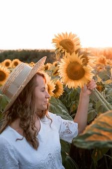 Seitenansichtsfrau, die sonnenblumen hält