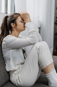 Seitenansichtsfrau, die traurig schaut, während sie von zu hause aus arbeitet