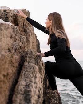 Seitenansichtsfrau, die über felsen klettert