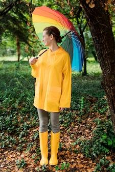 Seitenansichtsfrau, die weg schaut, während sie einen regenschirm hält