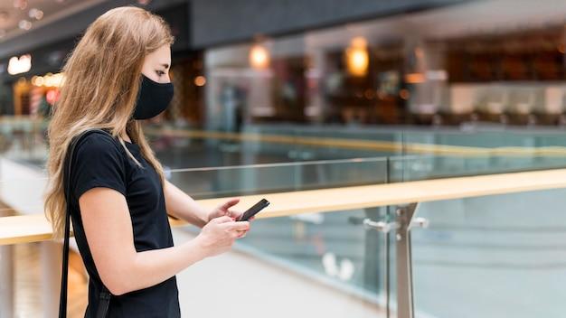 Seitenansichtsfrau im einkaufszentrum, das maske trägt