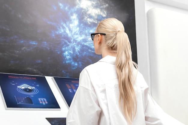 Seitenansichtsfrau mit der digitalen brille, die am monitor arbeitet
