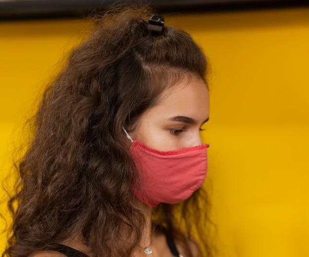 Seitenansichtsfrau mit der medizinischen maske, die in einem kaffeehaus arbeitet