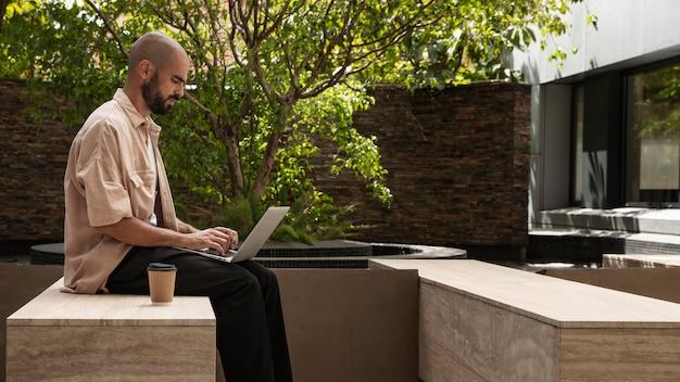 Seitenansichtsmann, der am laptop arbeitet