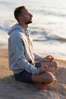 Seitenansichtsmann, der am strand meditiert