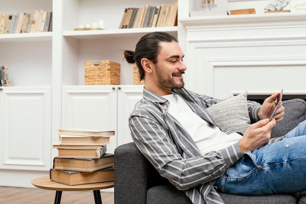 Seitenansichtsmann, der auf der couch mit einer tablette sitzt