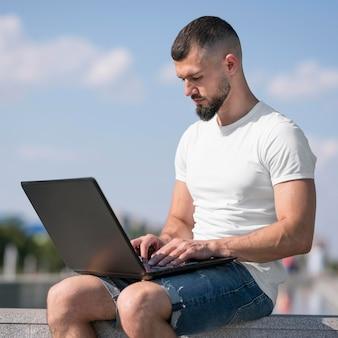 Seitenansichtsmann, der draußen an seinem laptop arbeitet