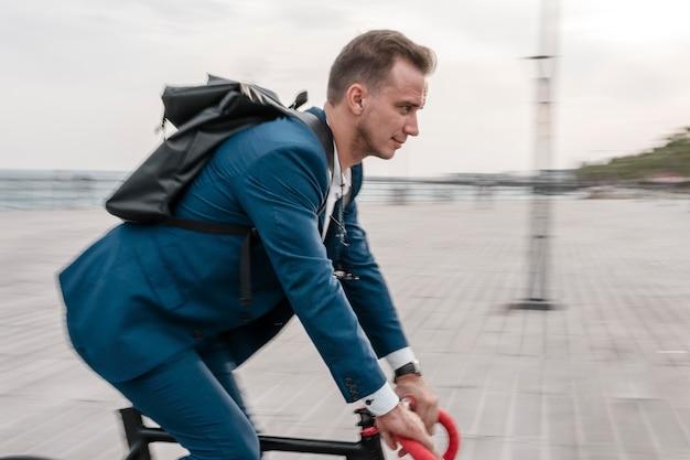 Seitenansichtsmann, der ein fahrrad zur arbeit reitet
